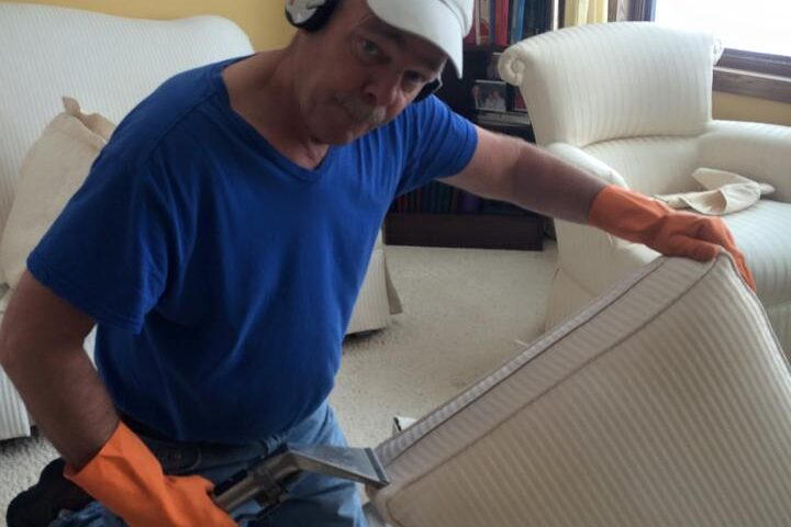 An image of Jim Swanson Founder and Owner of Swanson Pro Clean, cleaning a white couch cushion.